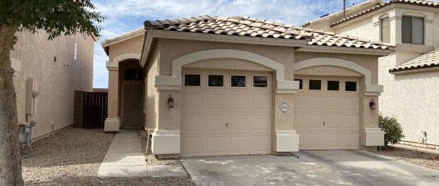 front view of a beige house with garage and front entrance